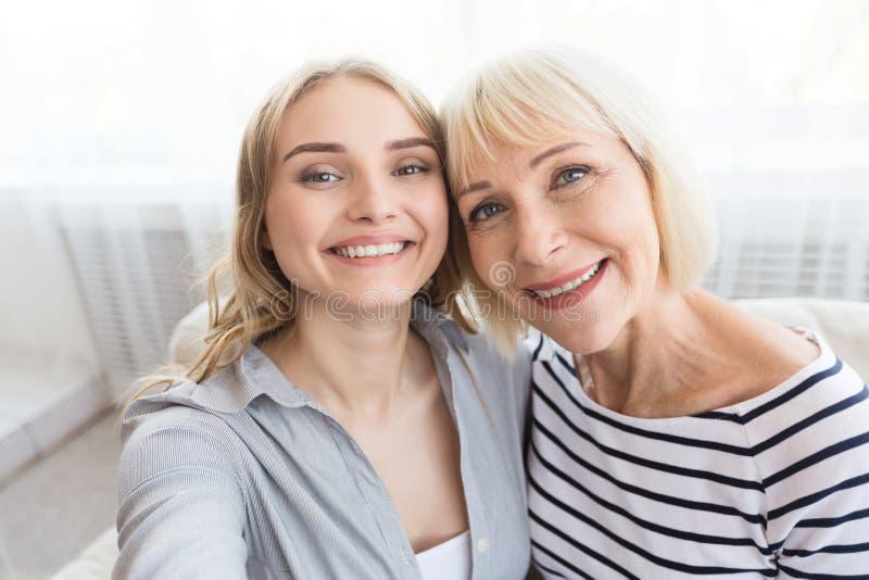Madre mayor e hija que toman el selfie en casa imágenes de archivo libres de regalías