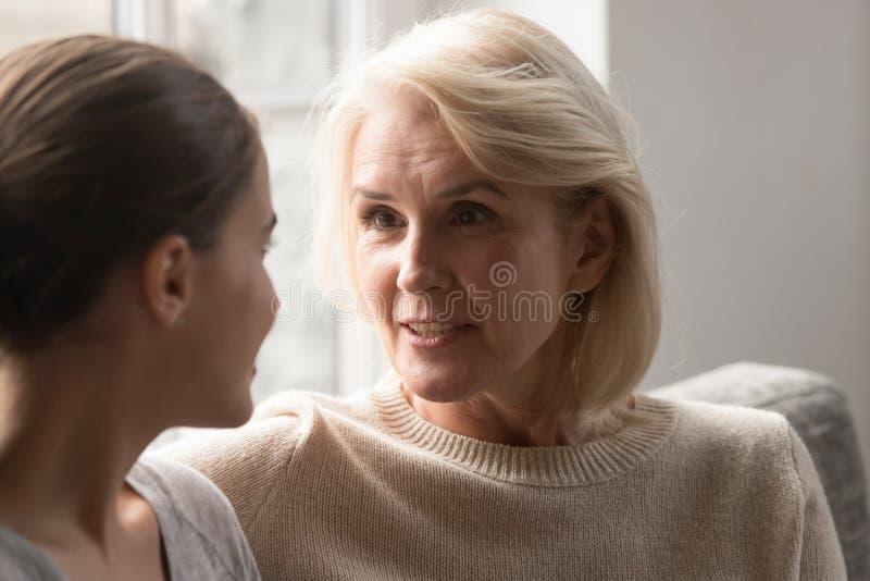 Madre mayor que charla con crecido encima de la hija que se sienta en el sofá fotografía de archivo