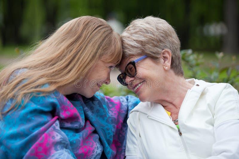 Madre mayor sonriente e hija joven que tienen ojo al contacto visual mientras que se sienta comparativo imágenes de archivo libres de regalías