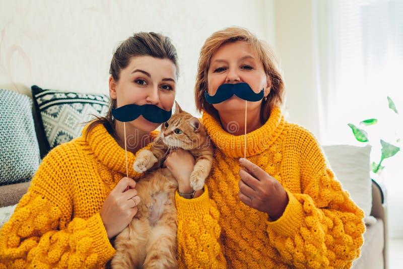 Madre mayor y su hija adulta que toman el selfie con el gato usando apoyos de la cabina de la foto en casa Concepto del d?a del ` foto de archivo