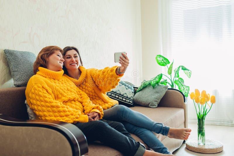 Madre mayor y su hija adulta que toman el selfie usando smartphone en casa Concepto del d?a del ` s de la madre foto de archivo libre de regalías