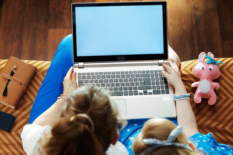 Madre moderna e hija que miran la pantalla en blanco en el ordenador portátil imágenes de archivo libres de regalías