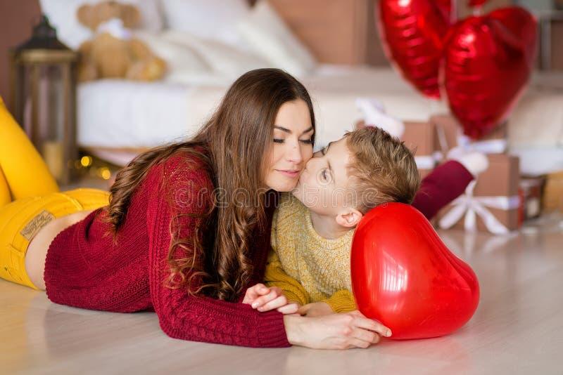 Madre morena joven linda de la mamá con su muchacho hermoso del adolescente que se mantiene y feliz hermosos unido Mujer adentro foto de archivo libre de regalías