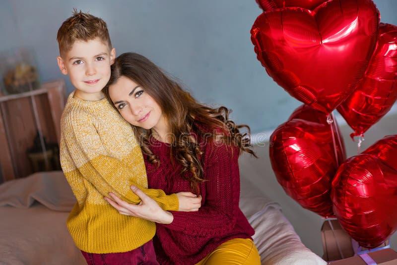 Madre morena joven linda de la mamá con su muchacho hermoso del adolescente que se mantiene y feliz hermosos unido Mujer adentro imagen de archivo libre de regalías