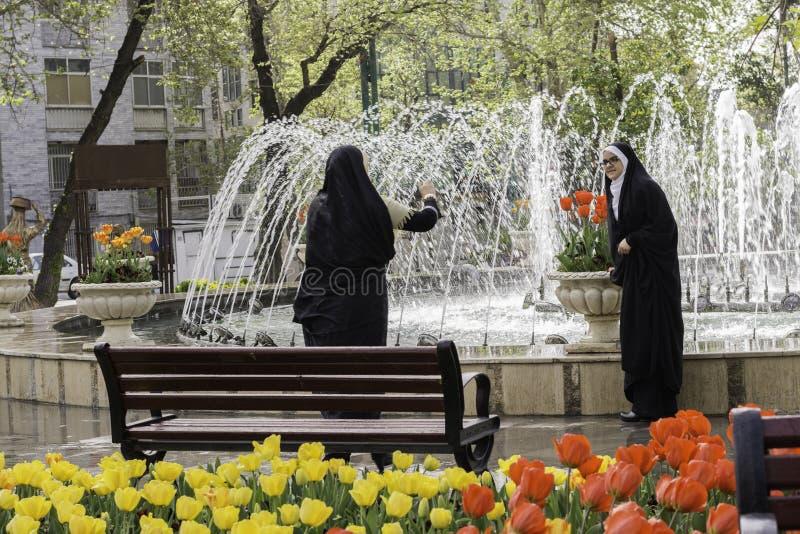 Madre musulmana che prende una fotografia di sua figlia dal cellulare a immagini stock