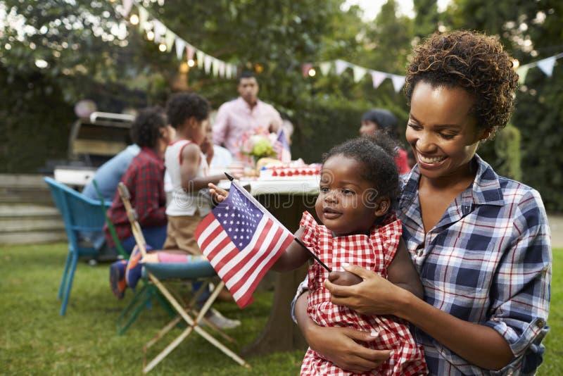 Madre negra y bebé que sostienen la bandera en la fiesta de jardín del 4 de julio imagenes de archivo
