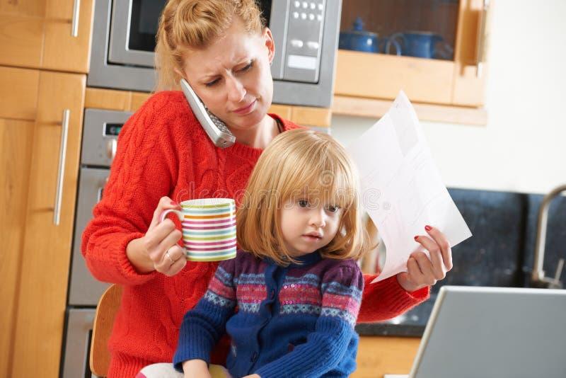 Madre occupata che fa fronte al giorno stressante a casa fotografie stock libere da diritti