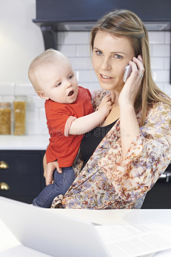 Madre occupata con il bambino che fa fronte al giorno stressante a casa fotografia stock libera da diritti