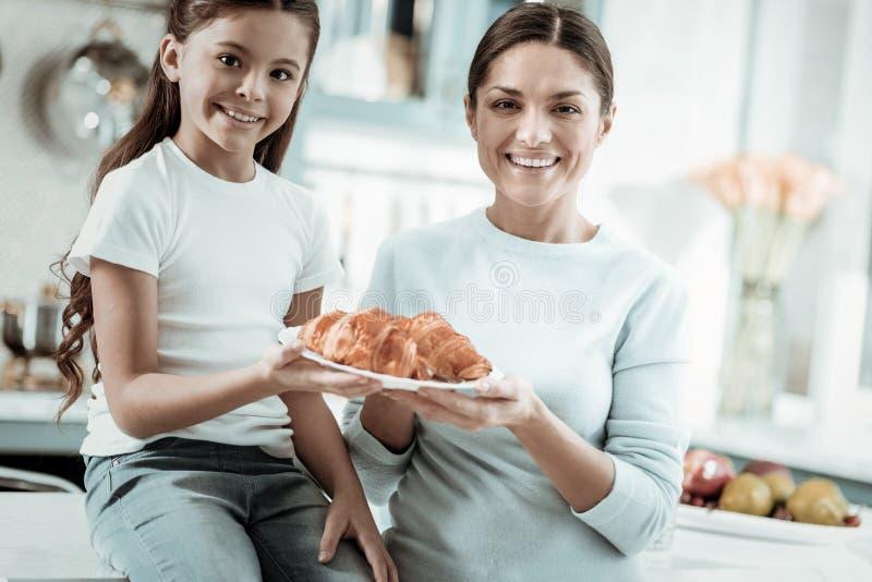 Madre orgullosa e hija que desayunan en la cocina imagenes de archivo