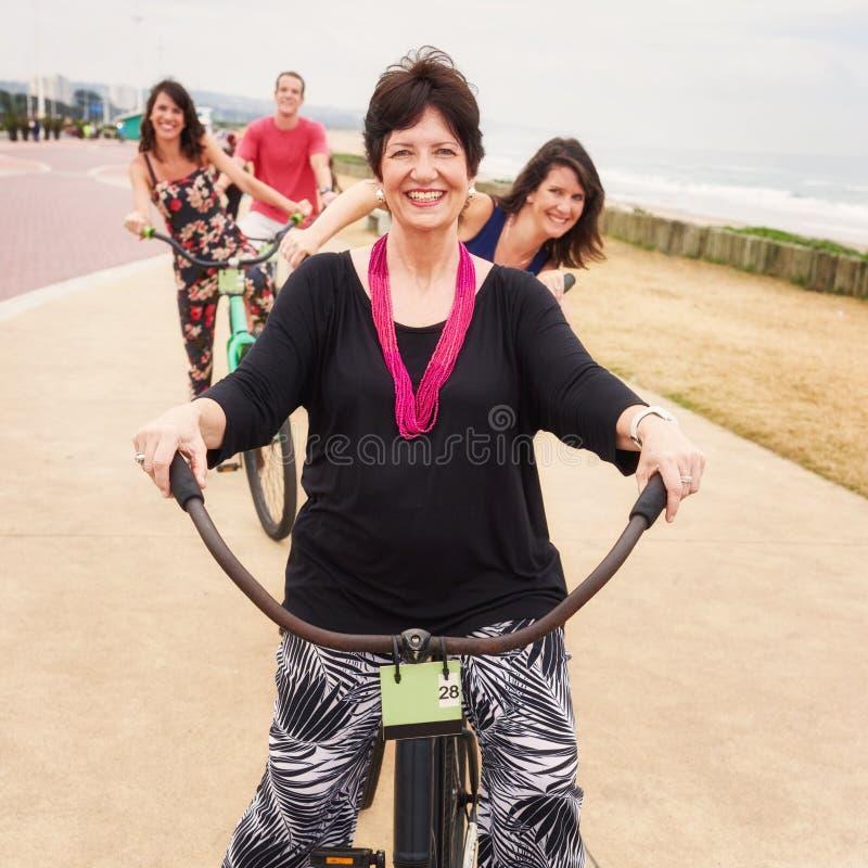 Madre orgullosa y sus tres niños felices en las bicicletas imagenes de archivo