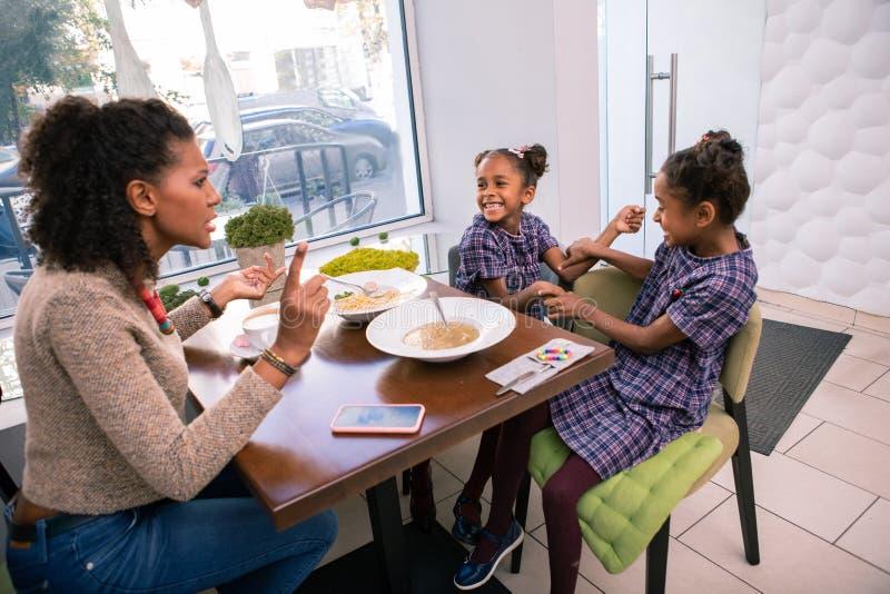 madre Oscuro-cabelluda que dice a sus muchachas comportarse buen sentarse en cafetería imágenes de archivo libres de regalías