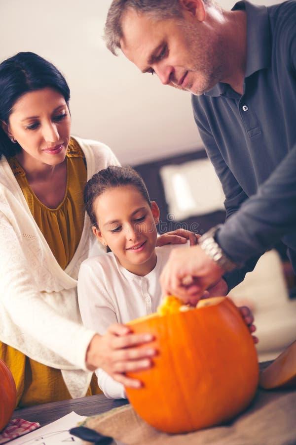 Madre, padre e figlia scolpenti zucca arancio fotografia stock libera da diritti