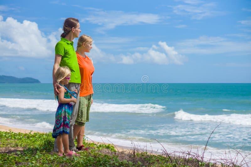 Madre, padre e hija en la playa tropical que lleva a cabo las manos con imagen de archivo