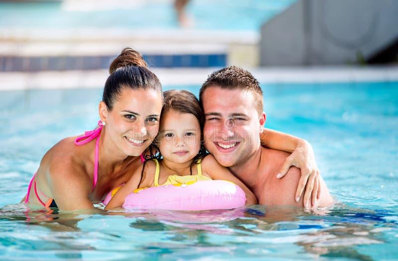 Madre, padre e hija en piscina Verano asoleado imagen de archivo libre de regalías