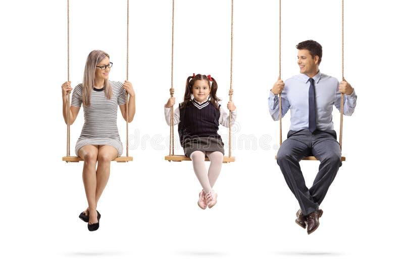 Madre, padre e hija sentándose en oscilaciones imágenes de archivo libres de regalías