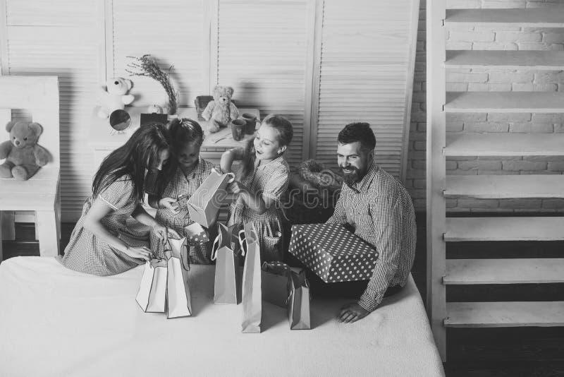 Madre, padre e hijas con los panieres y los paquetes fotografía de archivo