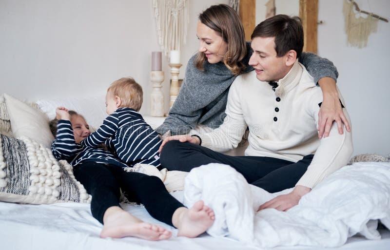 Madre, padre, figlio felice e figlia pieni della famiglia sedentesi sul pavimento alla notte di Natale Ritratto di natale fotografie stock