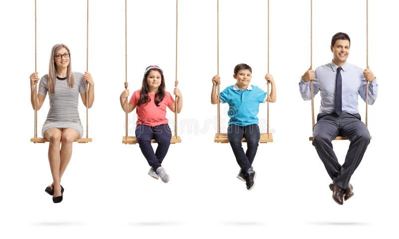 Madre, padre, hija e hijo sentándose en oscilaciones y sonriendo en la cámara imagen de archivo libre de regalías