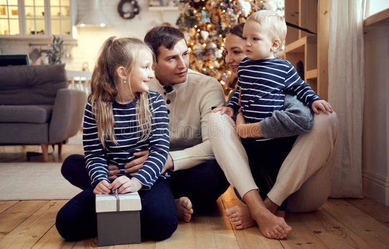 Madre, padre, hijo feliz e hija llenos de la familia sentándose en el piso en la Nochebuena Retrato de la Navidad foto de archivo