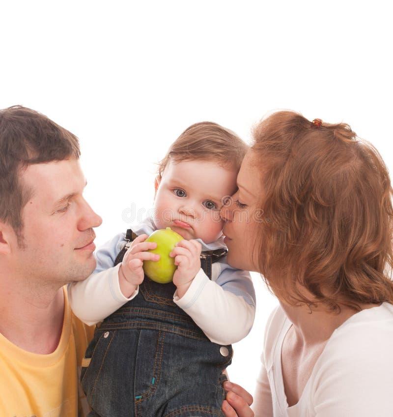 Madre, padre y bebé con la manzana verde imagenes de archivo