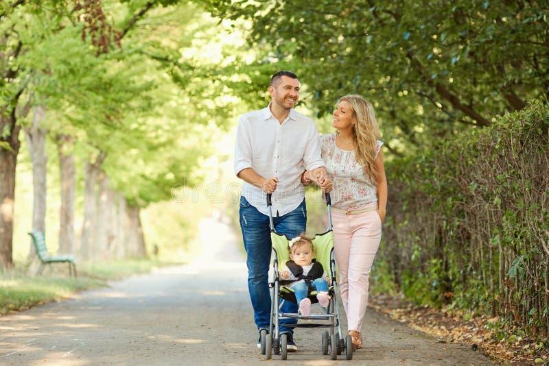 Madre, padre y bebé en un cochecito que camina en el parque fotos de archivo libres de regalías