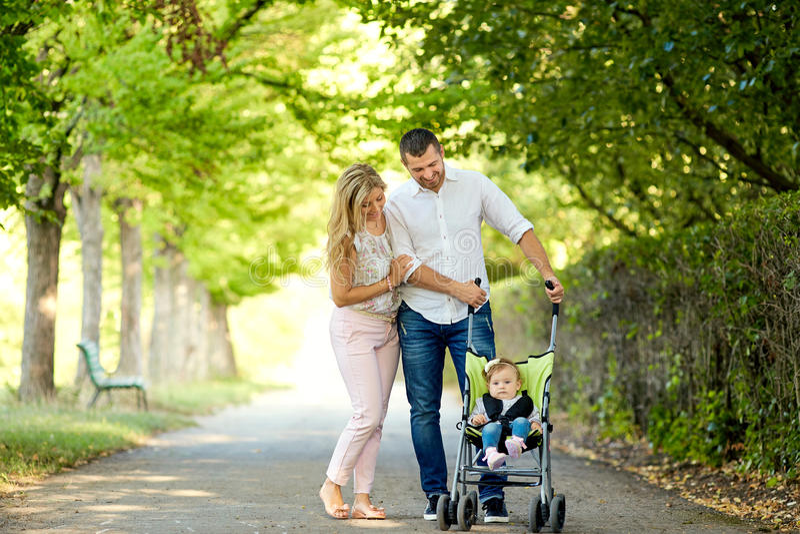 Madre, padre y bebé en un cochecito que camina en el parque imágenes de archivo libres de regalías