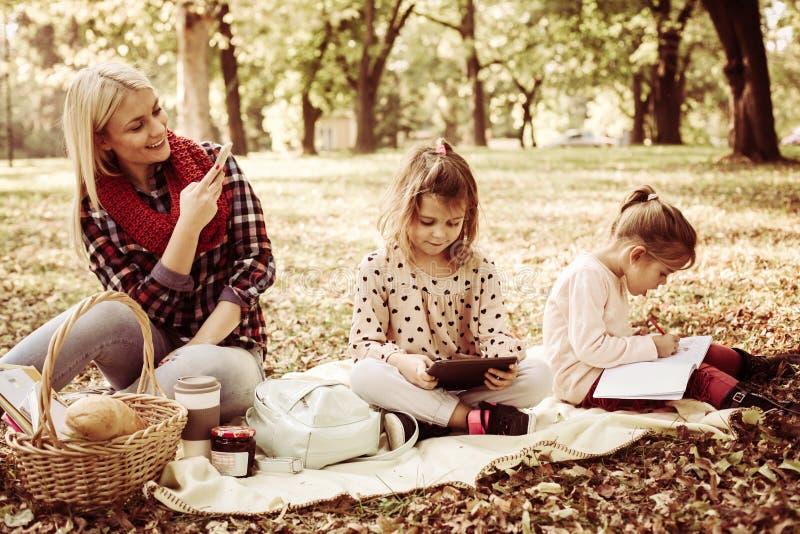 Madre in parco con le sue figlie che prendono immagine loro fotografia stock libera da diritti
