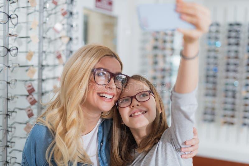 Madre positiva di amore che fa selfie con sua figlia immagini stock libere da diritti