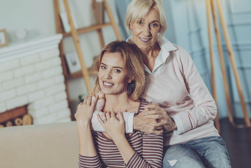 Madre positiva que abraza a su estimada hija imágenes de archivo libres de regalías