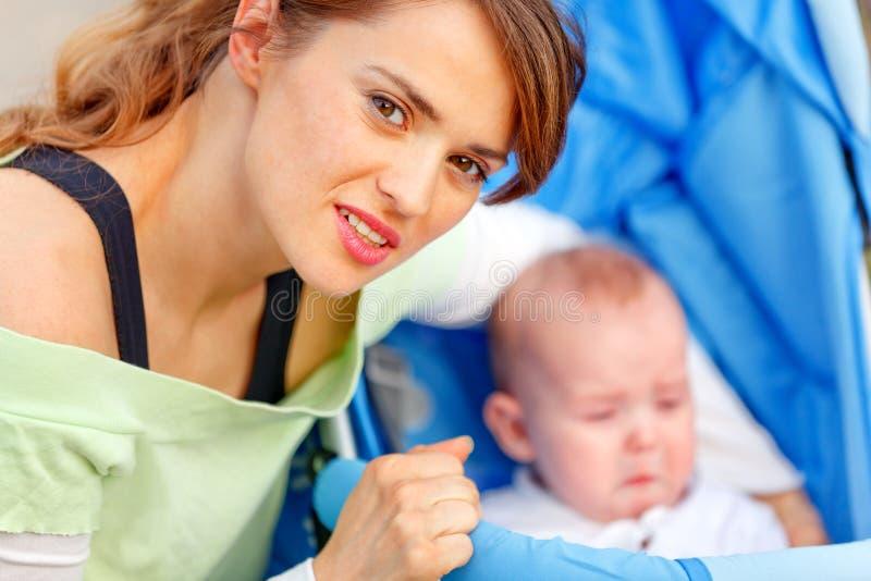 Madre preoccupantesi che abbraccia seduta nel bambino del passeggiatore immagini stock libere da diritti