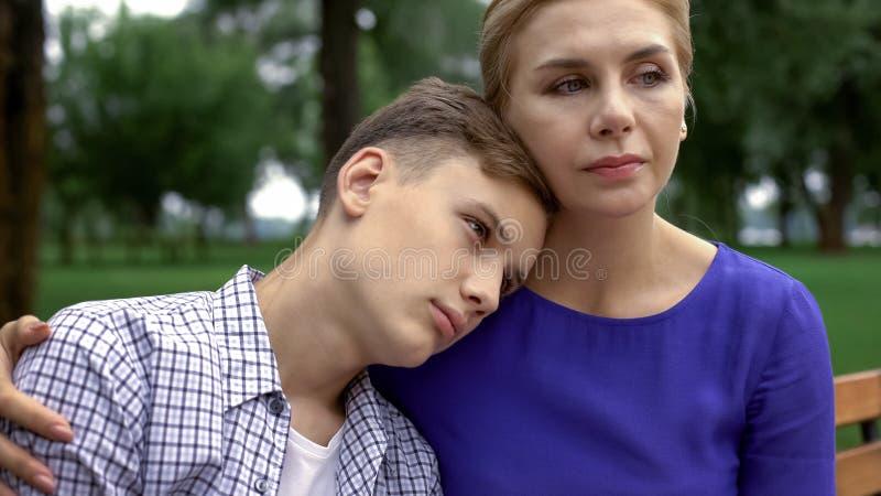 Madre preoccupantesi che sostiene ragazzo teenager in tempo di difficoltà, problema d'oppressione a scuola fotografie stock
