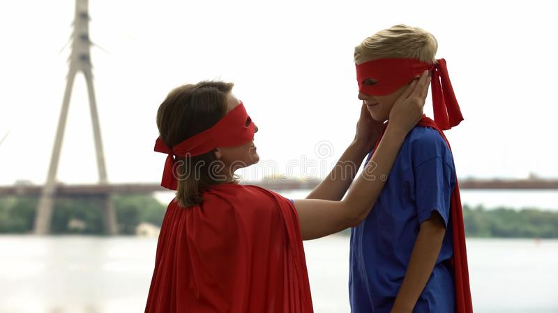 Madre preoccupantesi in costume del supereroe che esamina con l'amore il figlio, fiero del suo bambino immagini stock