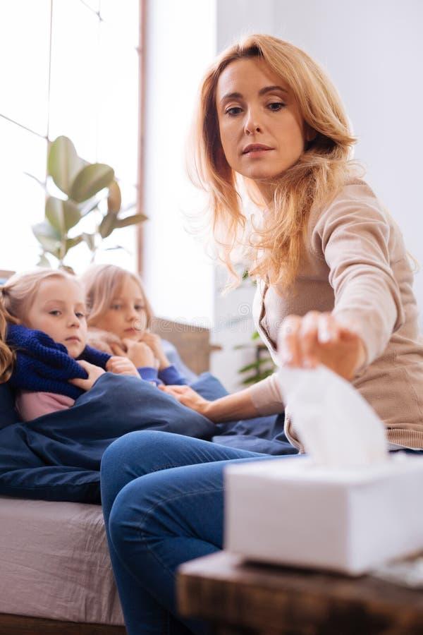 Madre preoccupata che si siede vicino ai suoi bambini malati fotografia stock