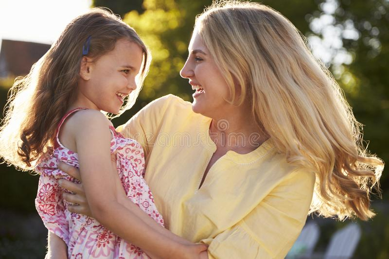 Madre que abraza a la hija al aire libre en jardín del verano fotografía de archivo libre de regalías