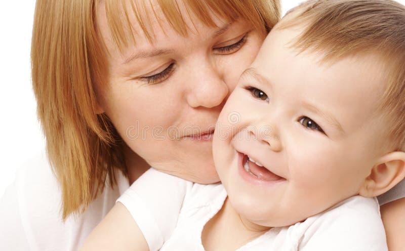 Madre que abraza a su niño feliz imagenes de archivo