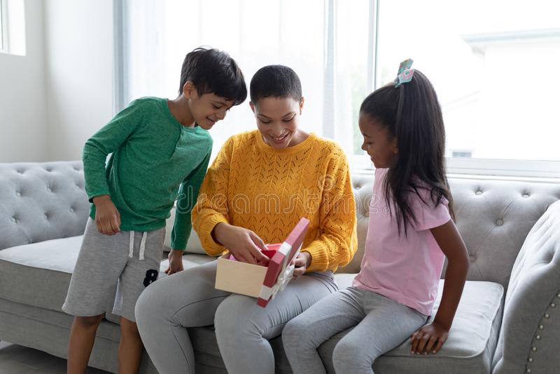 Madre que abre una caja de regalo con sus niños en sala de estar en casa fotografía de archivo