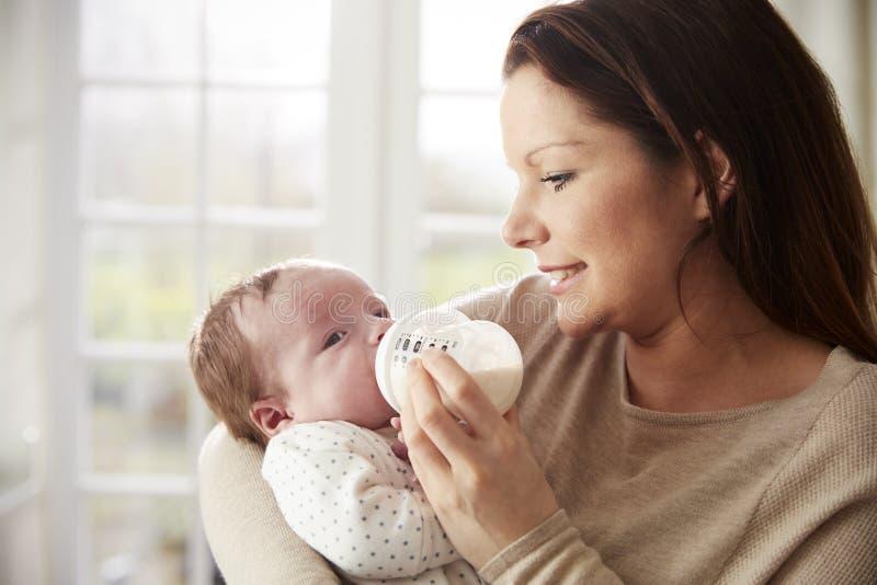 Madre que alimenta al bebé recién nacido de la botella en casa imagenes de archivo