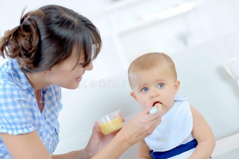 Madre que alimenta a la pequeña hija imagen de archivo libre de regalías