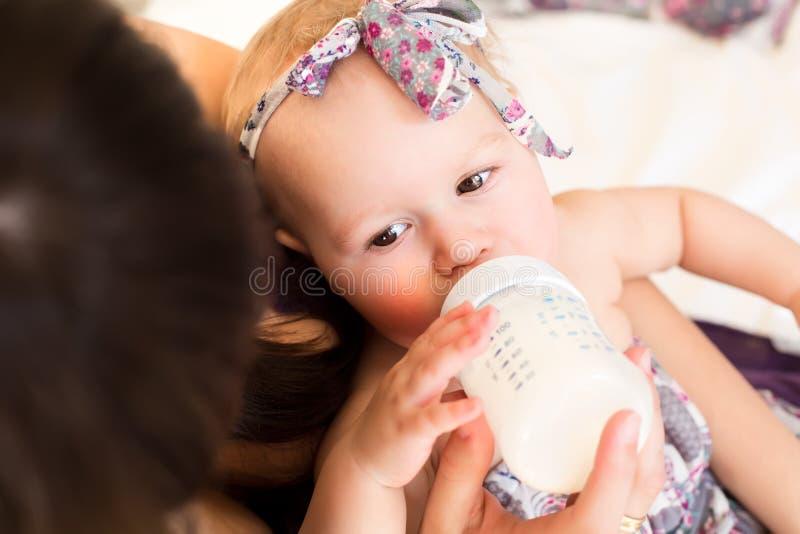 Madre que alimenta a su pequeño bebé fotos de archivo