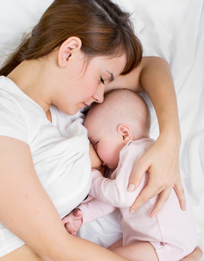 Madre que amamanta y que abraza a su bebé foto de archivo