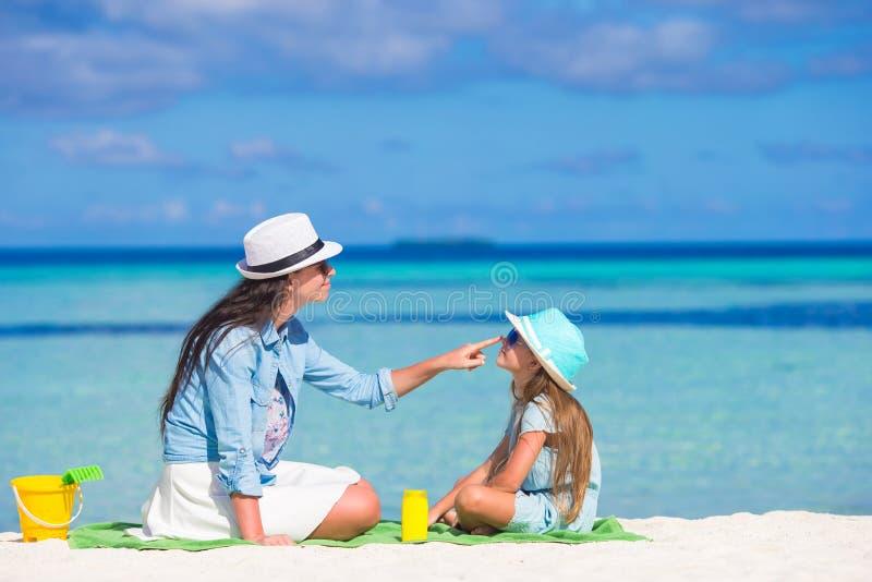 Madre que aplica la crema de la protección del sol a ella fotos de archivo