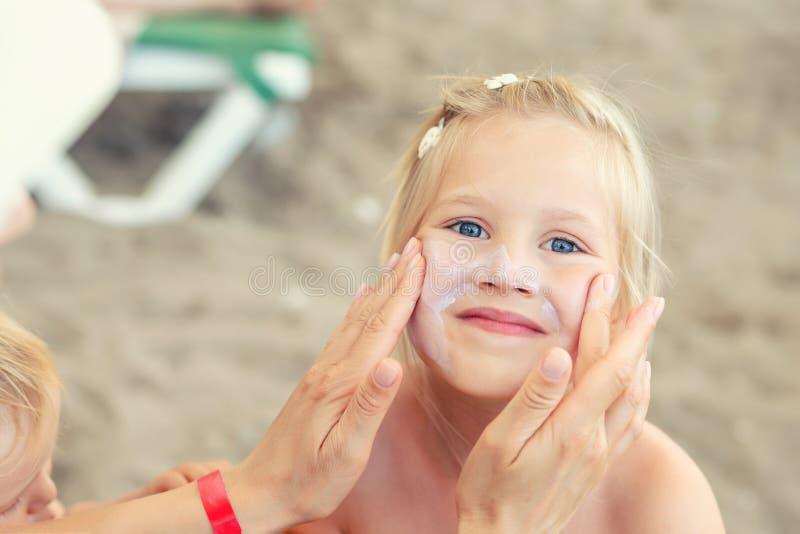 Madre que aplica la nata de la protección de la protección solar en pequeña cara linda de la hija Mamá que usa la loción sunblock fotos de archivo libres de regalías