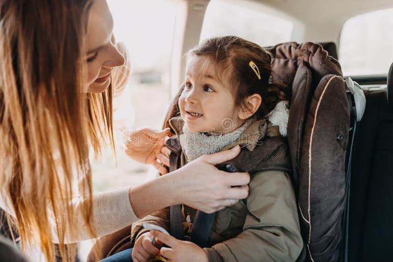 Madre que asegura a su hija del niño abrochada en su asiento de carro del bebé imagenes de archivo