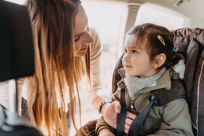 Madre que asegura a su hija del niño abrochada en su asiento de carro del bebé fotos de archivo