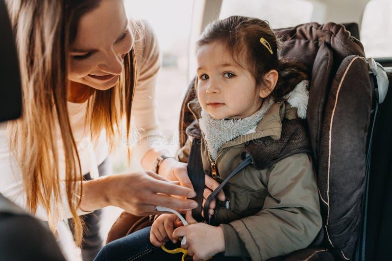 Madre que asegura a su hija del niño abrochada en su asiento de carro del bebé fotografía de archivo libre de regalías
