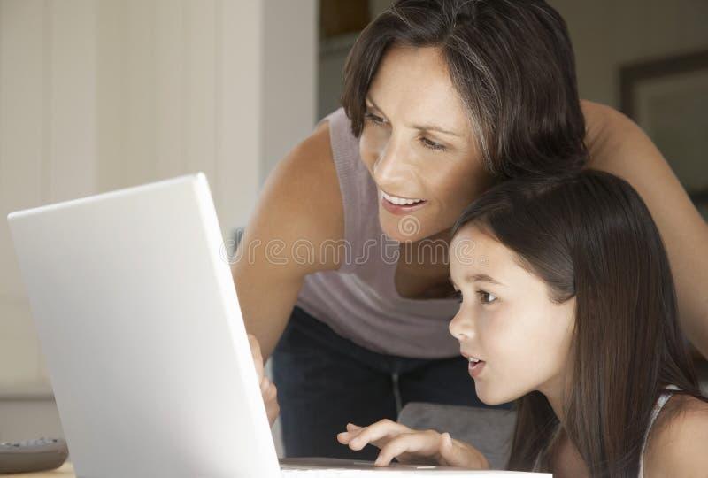 Madre que ayuda a la hija al usar el ordenador portátil imagenes de archivo