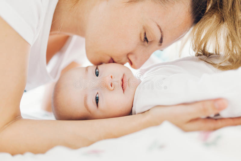 Madre que besa al bebé en mejilla fotos de archivo libres de regalías
