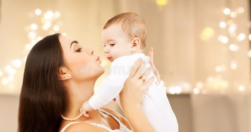 Madre que besa al bebé sobre luces de la Navidad imagenes de archivo