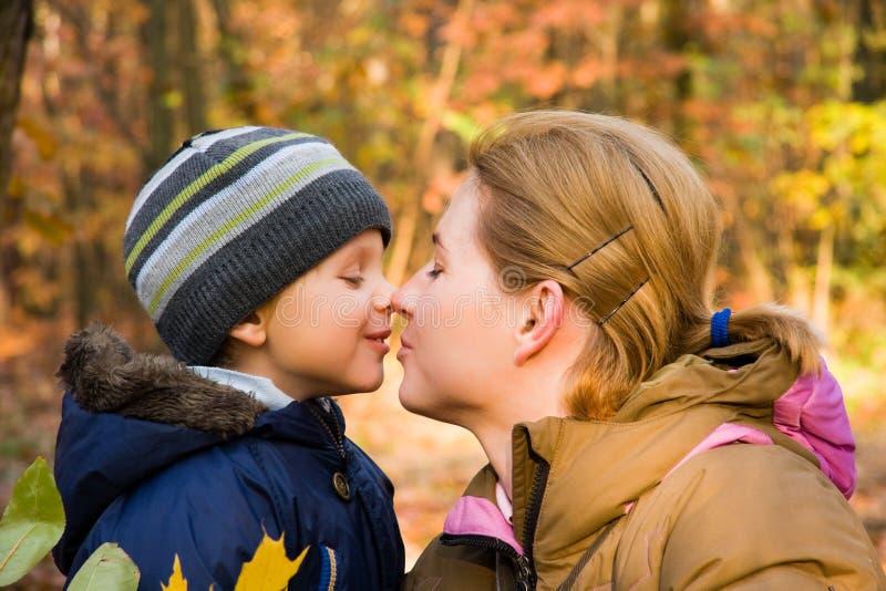 Madre que besa al hijo en paisaje del otoño foto de archivo