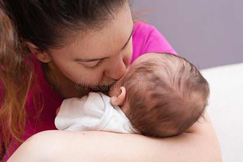 Madre que besa cariñosamente a su bebé recién nacido imágenes de archivo libres de regalías
